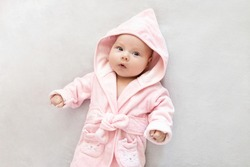 laughing baby girl in a Terry robe and diaper after bathing. Kid in a hood. Cute happy laughing baby girl in pink soft robe after bath. Baby in a clean and dry towel.baby hygiene, health and skin care
