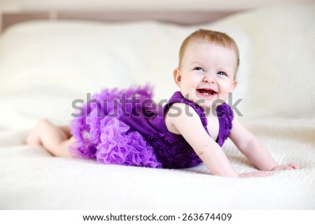 Laughing baby girl in purple dress on white bed