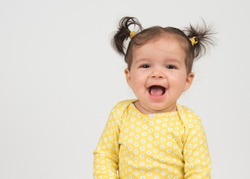 Laughing baby girl in yellow shirt on white background