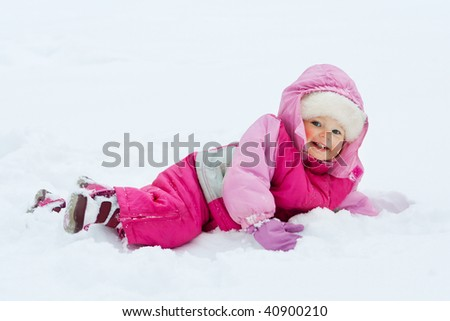 Laughing baby girl lying in deep snow