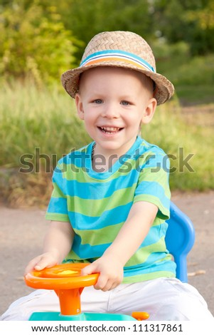 Laughing baby  in a hat driving a toy car