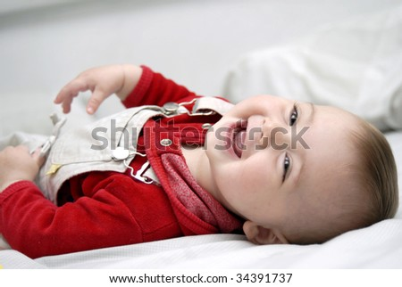 laughing baby laying on the bed