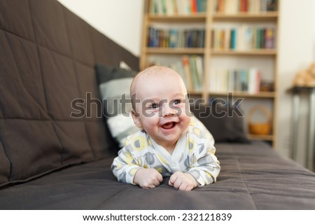 laughing baby on sofa, Beautiful smiling cute baby, expressive adorable happy child in child\'s room, blurry background