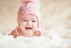 Laughing baby under 1 year old wearing knitted pink hat lying in bed closeup. Looking at camera. Happiness. Childhood.