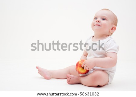 laughing baby with apple sitting on the floor
