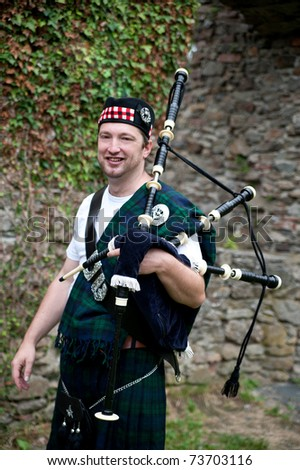 Laughing Bagpiper in front of a stone wall