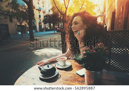 Laughing beautiful white caucasian girl with black curly hair and teal ring sitting in street cafe next to wooden table with cup and teapot of tea, sunny summer day in Barcelona, Born district, Spain