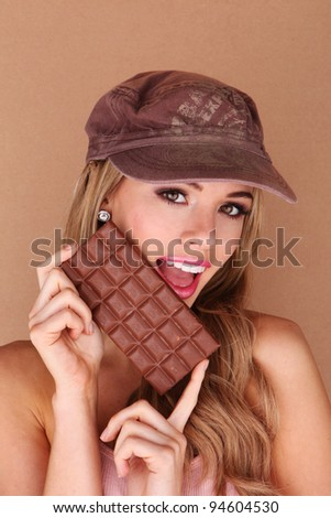 Laughing beautiful woman holding a slab of unwrapped chocolate close to her face.