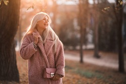 Laughing blonde beautiful girl 24-25 year old wearing winter coat walking in park outdoors. Winter season. Happiness.