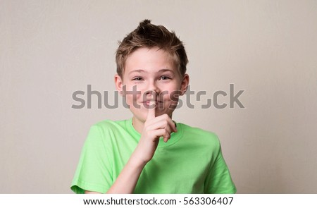 Laughing boy doing a silence gesture. Kid putting finger up to lips and ask silence. #563306407