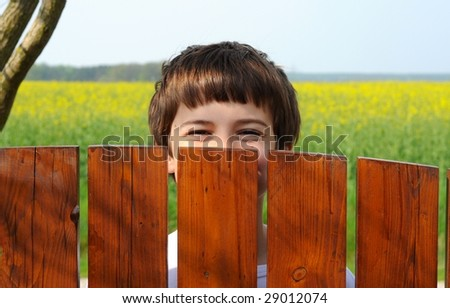 Laughing boy hides his face behind a wooden fence in order to hoax the photographer