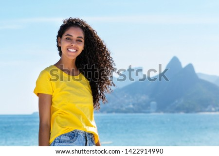 Laughing brazilian woman at Ipanema beach at Rio de Janeiro with beach and mountain in summer