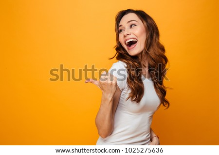Laughing brunette woman in t-shirt looking and pointing away with thumb over yellow background #1025275636