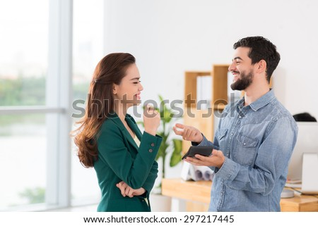 Laughing business colleagues counting income of the company