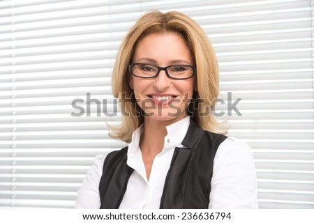 Laughing business woman in white shirt. Attractive mature businesswoman on white shutters smiling