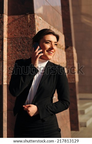 Laughing business woman talking by mobile outdoor
