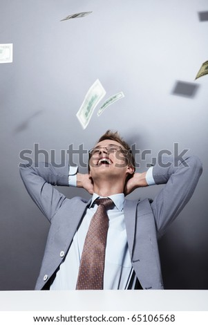 Laughing businessman on a background of flying money