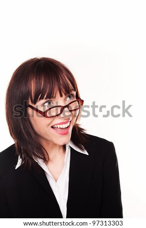 Laughing businesswoman looking up over the top of her glasses or spectacles into blank copyspace above her head - stock photo