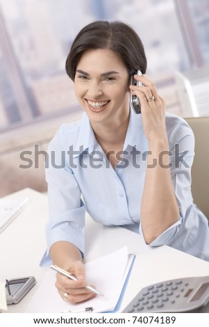 Laughing businesswoman on mobile phone call, sitting in office at desk, taking notes.