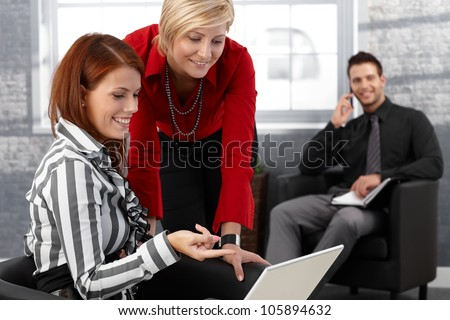 Laughing businesswomen using laptop computer in office lobby businessman in background.