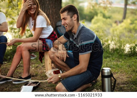 laughing carefree man is sitting with a stick on the grass. close up side view photo. free time