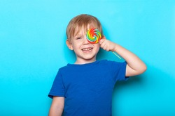 Laughing Caucasian child kid boy close one eye bright colorful lollipop candy. Close-up studio shot on blue background.