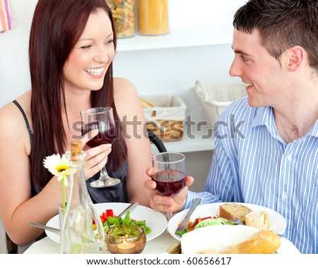 Laughing caucasian couple having dinner at home in the kitchen