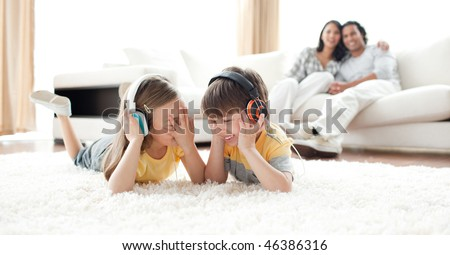 Laughing children listening music with headphones lying on the floor