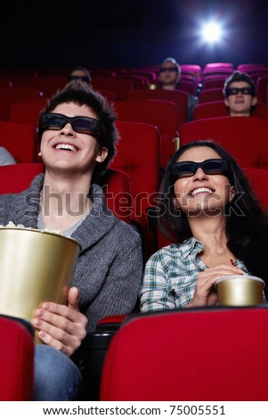 Laughing couple in 3D glasses in cinema