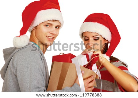 Laughing couple in Santa hats with presents isolated on white background