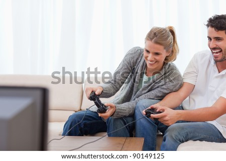 Laughing couple playing video games in their living room