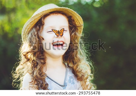 Laughing curly girl with a butterfly on his hand. Happy childhood concept. Background toning for instagram filter.