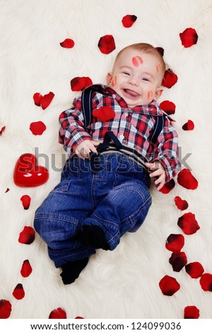 Laughing cute boy with lipstick on his face lying with rose petals.