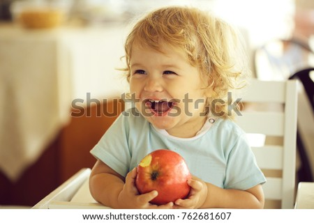 Laughing cute fair-haired blond hazel-eyed kid little child baby boy sitting in highchair and eating big red apple fruit portrait on blurred background, horizontal picture