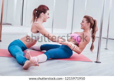 Laughing dancers. Two beautiful experienced pole dancers laughing while helping each other stretching legs