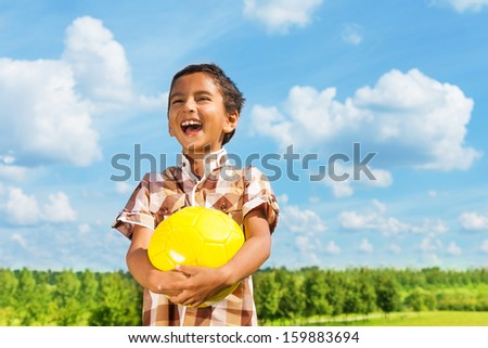 Laughing dark boy holding yellow volley ball standing in the park on sunny day with blue clouds on background