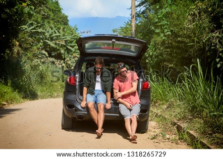 Laughing dudes in trunk of car on road trip