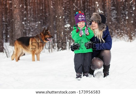 Laughing family and german shepherd dog in winter park