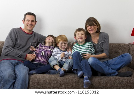 Laughing family is sitting on the sofa