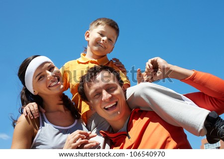 Laughing family of three having fun together on a sunny summer day