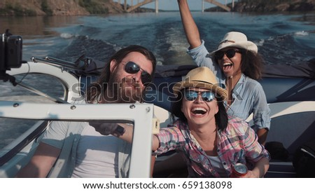 Laughing family or three friends wearing sunglasses riding in a speedboat on a lake or river as they celebrate their summer vacation viewed close up