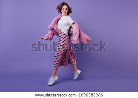 Laughing fascinating girl in white sneakers jumping on purple background. Full-length photo of enthusiastic young woman with wavy hair dancing in studio.