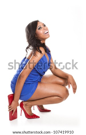 Laughing fashionable African woman in a short blue dress with red stilettoes and matching purse crouching down on the floor isolated on white