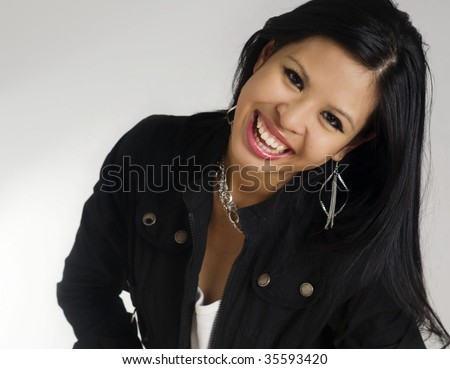 Laughing female captured in candid moment  during portrait shoot of a beautiful Asian young female student, taken in studio.