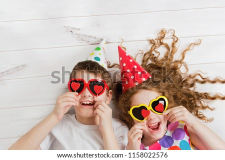 Laughing girl and boy with sunglasses, hold candles heart form, lying on the wooden floor. Christmas, New Year or Valentines day concept. #1158022576