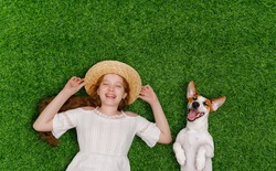 Laughing girl and cute dog enjoy summer day on the grass in the park. Spring, Easter background. Top view portrait.