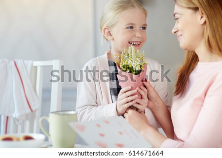 Laughing girl giving her mother bunch of wildflowers #614671664