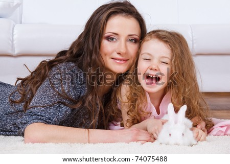 Laughing girl, her mother and  a white bunny lying