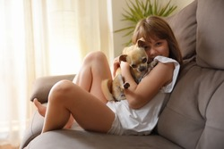 Laughing girl holding her dog affectionately on the sofa looking at camera