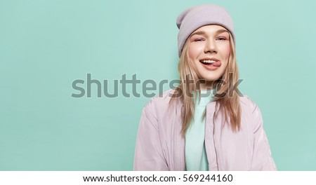 Laughing girl in a  in stylish casual clothes and shows tongue